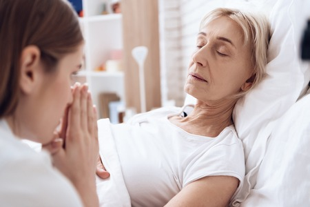 Girl is nursing elderly woman in bed at home. Woman is feeling bad, girl is worried about her.