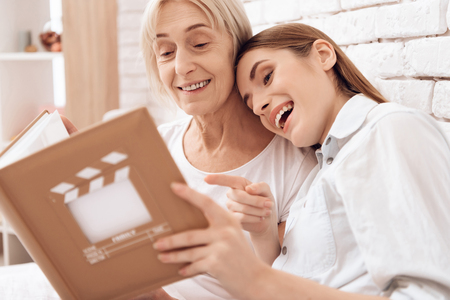Girl is nursing elderly woman in bed at home. They are watching photos in photo album.