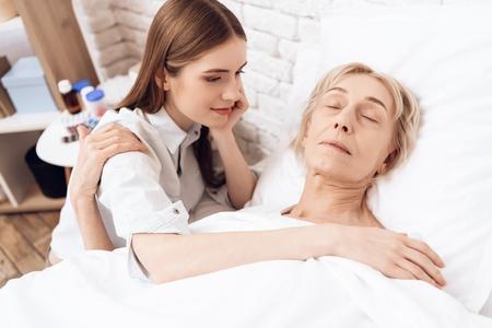 Girl is nursing elderly woman in bed at home. Woman is sleeping peacefully.