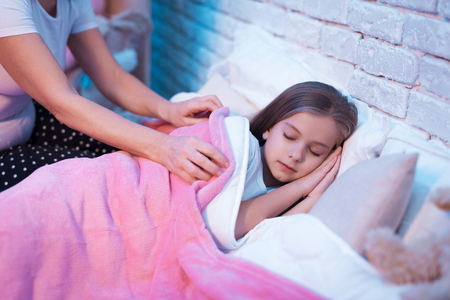 Grandmother tucking in granddaughter for sleep in bed at night at home. Stock Photo