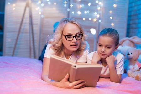 祖母と孫娘は、家で夜寝る前にベッドに横たわる本を読んでいます。