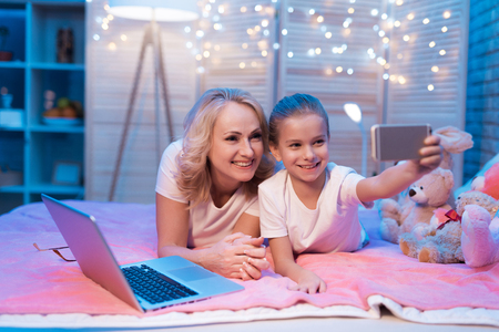 Grandmother and granddaughter are taking selfie on bed at night at home. Stock Photo