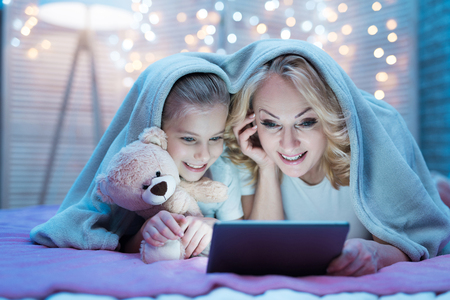Grandmother and granddaughter are watching movie on tablet under blanket on bed at night at home.
