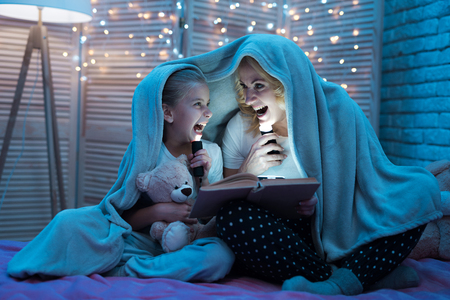 Grandmother and granddaughter are reading fairy tales under blanket on bed at night at home. Stock Photo
