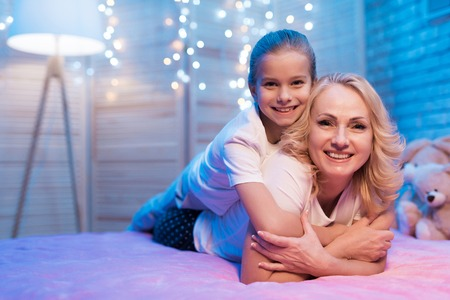 Grandmother and granddaughter are embracing each other on bed at night at home. 스톡 콘텐츠