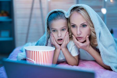 祖母と孫娘は、自宅で夜ベッドの上の毛布の下でラップトップで映画を見ています。