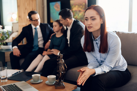 Frustrated mother in blue shit sits on couch next to adult father and daughter. Dissolution of marriage of two adults. Divorce of adult couple.