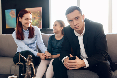Frustrated father with phone in hands sits on couch next to young wife and daughter. Dissolution of marriage of two adults. Divorce of adult couple.