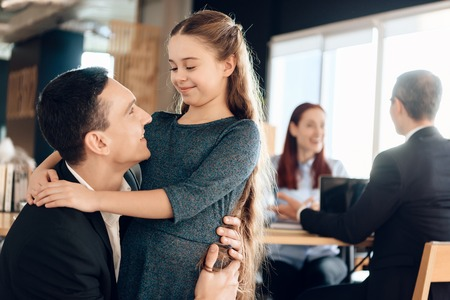 Adult father hugs little daughter, standing in foreground. Young family in office of lawyer. Young parents argue about one who will take guardianship of little daughter in lawyers office. Stock Photo