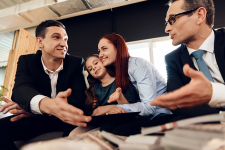 Red-haired woman hugs girl sitting between two adult men who agree on something. Happy family in office of family lawyer. Stock Photo