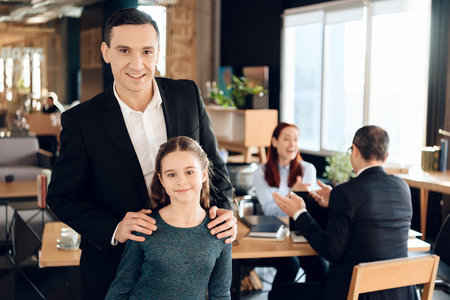 Joyful adult man is standing in foreground and hugging joyful girl in lawyers office. Family in office of family lawyer. Stock Photo