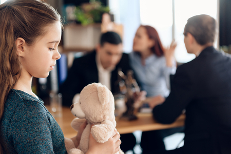 Young couple arranges guardianship of little girl. Registration of guardianship. Family in office of family lawyer. Two parents fighting over child in divorce concept. 스톡 콘텐츠