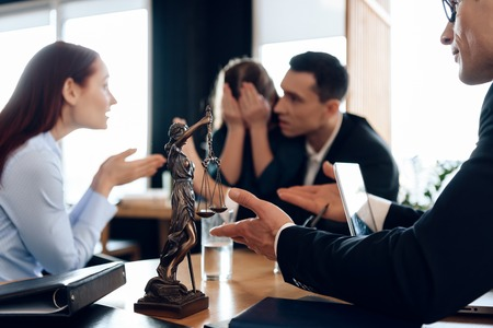 Bronze statue of Themis holds scales of justice. In unfocused background, couple divorce. Young parents argue about one who will take guardianship of little daughter in lawyers office.