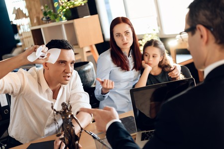 Stunned adult man smashes paper sitting at table next to woman hugging little girl. Adult couple gets divorced from attorney for divorce in office. Stock Photo - 97681692