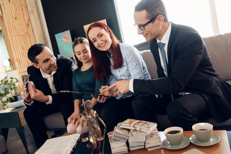 Authorized lawyer shows red-haired woman where she must to sign to receive money. Family in office of family lawyer. Property division.
