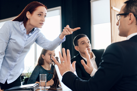 Enraged young woman is angry with family lawyer. Agitated young family communicates with lawyer. Young man and beautiful woman decide who will be main guardian of little girl. Reklamní fotografie