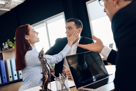 Wicked wife slaps surprised husband face, sitting at lawyers table to dissolve marriage. Adult couple gets divorced from attorney for divorce in office. Divorce of adult couple.