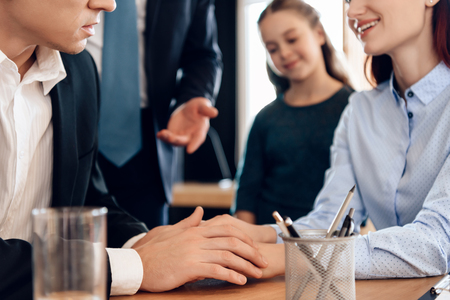Adult man looks at wedding ring while sitting in divorce lawyers office. Family in office of family lawyer. Young man and beautiful woman decide who will be main guardian of little girl.