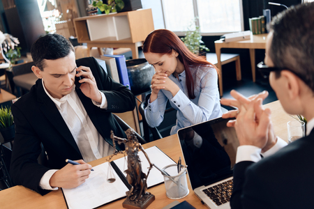 Man who divorces his wife consults on phone with lawyer. Upset woman sits next to man talking on phone. Divorcing couple dissolves marriage contract. Фото со стока