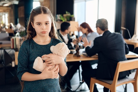 Little girl is hugging teddy bear at office of family lawyer. Registration of guardianship. Family in office of family lawyer. Banque d'images