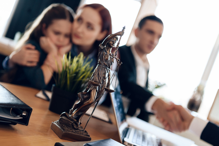 Bronze statue of Themis stands on table, behind which sits divorcing parents with little girl. Young man and beautiful woman decide who will be main guardian of little girl.