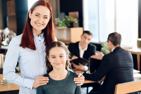 Joyful red-haired woman is standing in foreground and hugging joyful girl in lawyers office. Family in office of family lawyer.