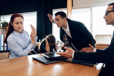 成人男性は弁護士事務所で子供を持つ女性に手を挙げた。成人カップルは離婚しています。大人2人を解散させる。 写真素材