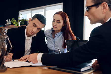 Divorce attorney shows man where to sign marriage dissolution agreement. Husband are signing divorce settlement. Adult couple is divorced.