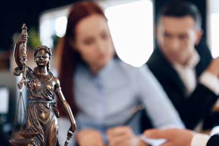 Bronze statue of Themis holds scales of justice. In unfocused background, couple signs documents. Couple going through divorce signing papers.
