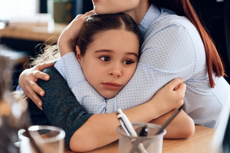 Young sad mother hugs little upset daughter sitting in lawyers office for divorce. Two parents fighting over child in divorce concept.