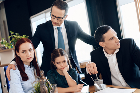 Lawyer calms family down with little girl who gets divorced. Family in office of family lawyer. Young man and beautiful woman decide who will be main guardian of little girl.
