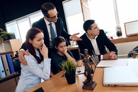 Lawyer calms family down with girl who gets divorced. Family in office of family lawyer. Adult man and beautiful woman decide who will be main guardian of little girl.