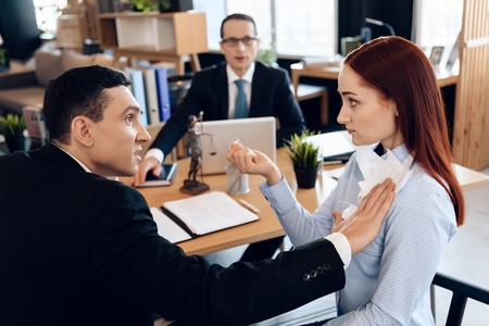 Disgruntled adult man pokes torn marriage contract into red-haired woman in divorce lawyers office. Dissolution of marriage of two adults. Divorce of adult couple.