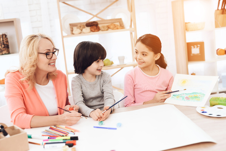 Beautiful egrandmother teaches grandchildren to draw. Children draw with paints. Drawing with paints. Little children draw. Painting. Stok Fotoğraf