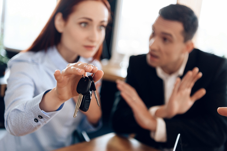 Keys of car hang on finger of woman hand who is in defocus. Property division. Concept of property division under divorce.