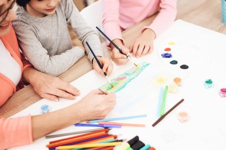 Beautiful elderly woman teaches children to draw. Little children draw. Drawing lessons. Grandmother teaches children to paint with watercolor. Drawing with paints. 写真素材