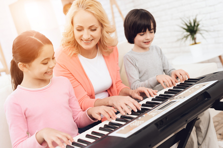 Lovely elderly woman teaches small grandchildren to play synthesizer. Young grandmother plays piano for her grandchildren.