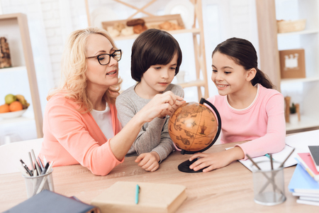 Beautiful middle-aged woman in pink blouse is pointing finger at mainland on globe. Beautiful grandmother studies geography with her grandchildren. Reklamní fotografie