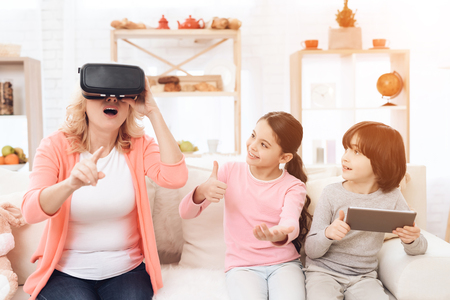 Surprised adult woman in virtual reality glasses sits on couch next to her granddaughter and grandson, who holds tablet. Elderly woman wearing virtual reality device.