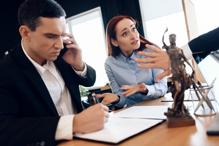 Man who divorces his wife consults on phone with lawyer. Disconcerted woman sits next to man talking on phone. Adult couple gets divorced from attorney for divorce in office. Фото со стока
