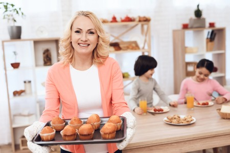 Beautiful elderly woman in pink blouse baked cupcakes for grandchildren who dine in kitchen. Young grandmother made cupcakes for grandchildren.
