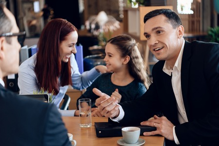 Confident father, red head mother and little smiling daughter are sitting in lawyers office. Family in office of family lawyer.