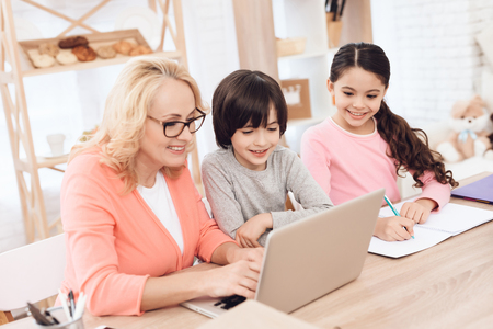 Beautiful elderly woman typing on laptop with her grandchildren. Education at home. Grandmother helps to make lessons for grandchildren. Stock Photo