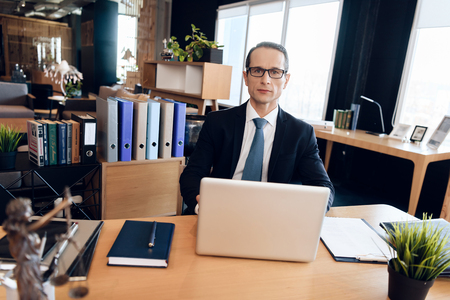Adult confident man in suit is sitting at table in office. Lawyer is at work. Attorney in business suit is sitting at laptop in lawyer office.