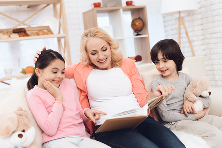 Beautiful grandmother looks at photo album with joyful granddaughter and grandson holding teddy bear. Young grandmother with grandchildren in mood watching photo album sitting on couch in room. Stock Photo
