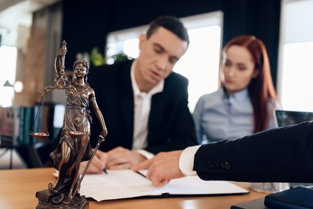 Statue of Themis holds scales of justice. In unfocused background, adult man signs documents. Divorcing couple dissolves marriage contract. Couple going through divorce signing papers.