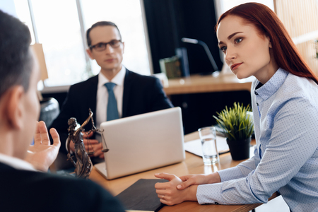 Red-haired beautiful woman listens attentively to man looking at divorce attorney. Attorney in business suit is sitting at office table, listening to discussion of divorcing couple.