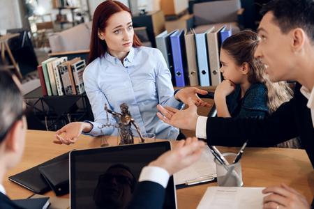 驚いた赤毛の女性は、弁護士事務所で男女の前で手を広げます。成人カップルは離婚しています。成人カップルは、在職中の離婚のために弁護士か 写真素材