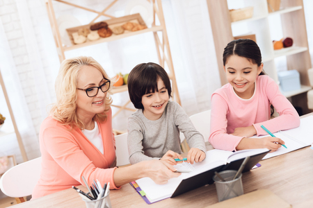 Grandmother helps to make lessons for grandchildren. Beautiful granny helps children learn. Education at home. Heavy homework at school. Decisions of school exercises.