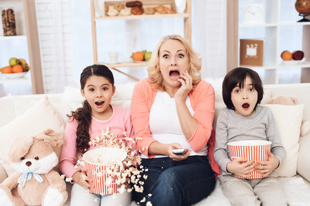 Young beautiful grandmother with her grandchildren eating popcorn and watching movie at home on couch. Home watching movie. Frightened elderly woman watches movie with her grandchildren. 写真素材